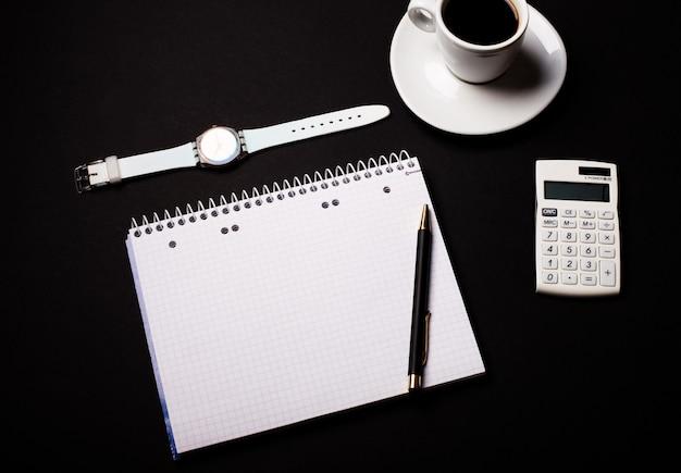 白いカップに入ったコーヒー、腕時計、電卓、黒い壁に開いた白紙のノート。コピースペース