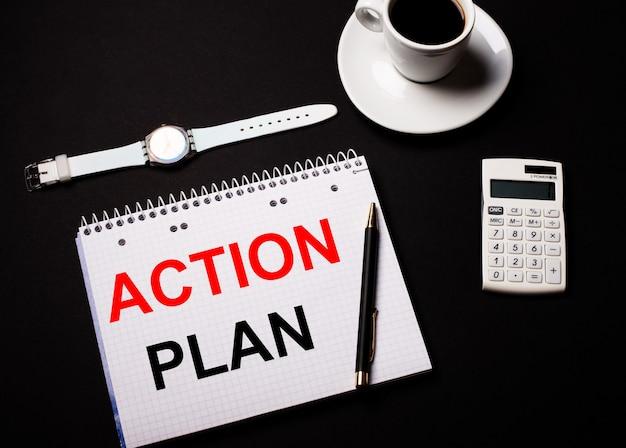 白いカップに入ったコーヒー、腕時計、黒いテーブルの上の電卓。近くには、actionplanというテキストが書かれたペンとノートがあります。