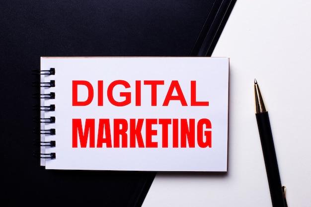 Кофе в белой чашке, наручные часы и калькулятор на черном столе. рядом ручка и блокнот с текстом цифровой маркетинг.