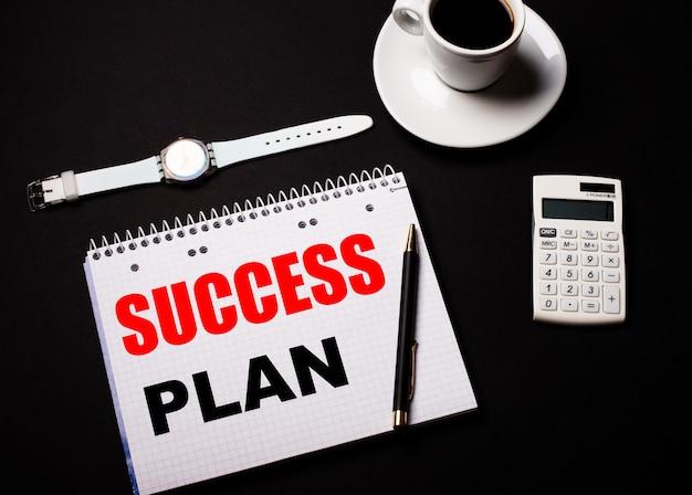 白いカップに入ったコーヒー、腕時計、黒いテーブルの上の電卓。近くには、successplanというテキストが書かれたペンとノートがあります。