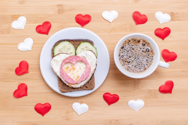 Кофе в белой чашке и бутерброд с яичницей в форме сердца, сосисками и огурцами на зеленой тарелке