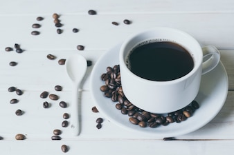 Coffee in a white cup and saucer. Spilled coffee beans, spoon.