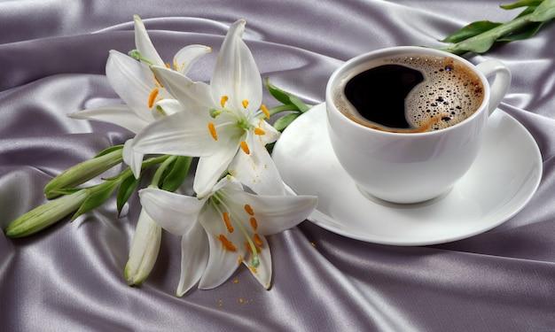 白いカップでコーヒー。一杯のコーヒーとシルクの背景に白いユリの花。ロマンチックなコーヒー。閉じる