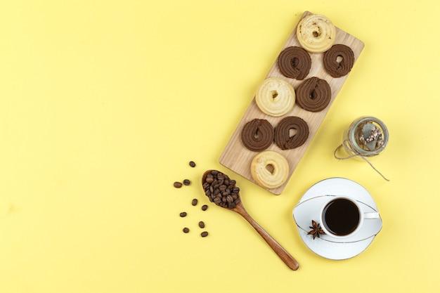 Кофе в чашке с кофейными зернами, печеньем, сушеными травами на желтом фоне