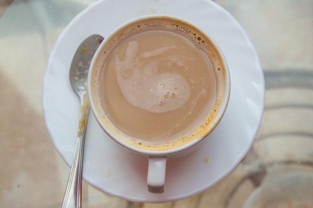 Кофе в чашках на стеклянном столе, вид сверху, на открытом воздухе.
