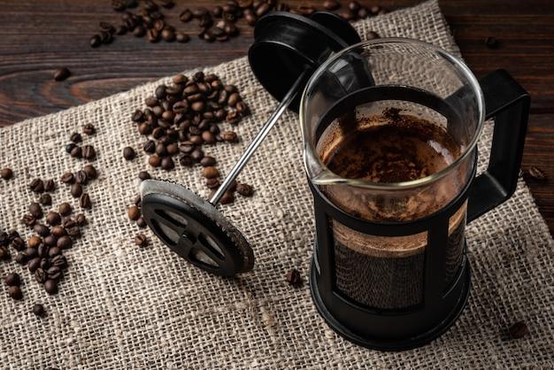 フレンチプレスのコーヒーとダークウッドの背景にコーヒー豆。