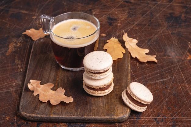 유리 컵에 든 커피와 나무 배경에 있는 초콜릿 마카롱. 아늑한 가을 구성 - 이미지