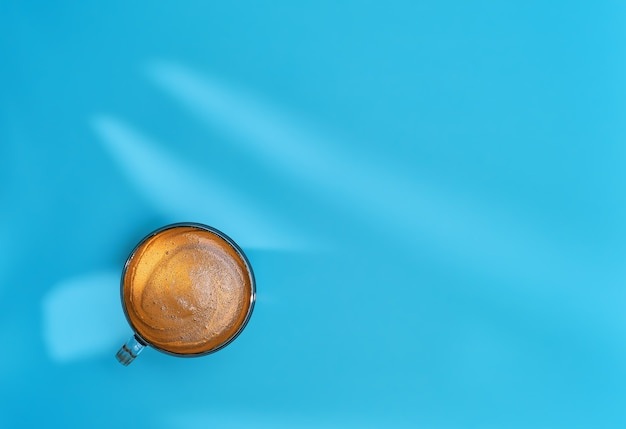 ガラスのカップに入ったコーヒーは、テーブルの上の葉からの影である明るい青色の背景に配置されています。芳香のあるクレマ、コピースペースのレイアウトを備えた強いエスプレッソ。