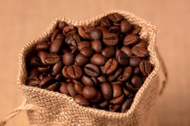 Кофе в мешке из рафии, коричневый фон
