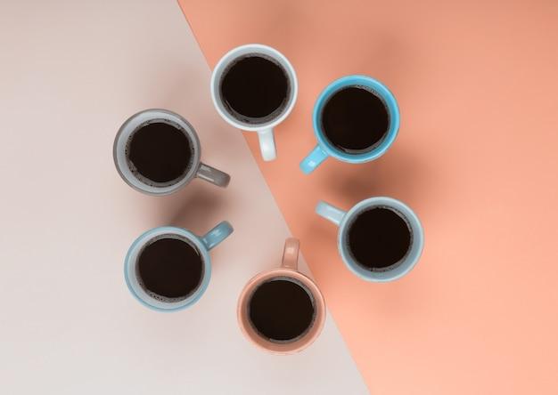 サンゴの背景に別のカップでコーヒー。 flatlay、陽気な日のコンセプト