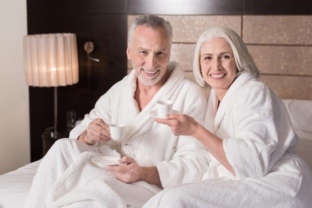 아침에 커피. 기쁨을 표현하면서 침대에 누워 커피를 마시는 명랑 웃는 세 커플