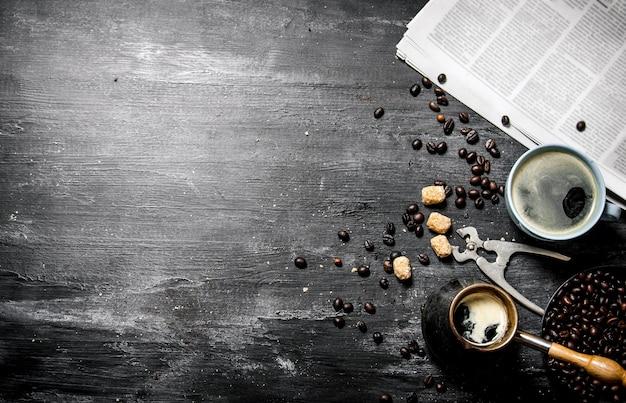朝のコーヒー。コーヒーポットと木製のテーブルの上に焙煎したコーヒー豆が入った新聞。