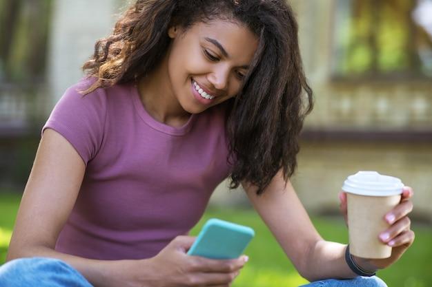 Кофе в парке. милая девушка в розовой футболке сидит на траве и пьет кофе Premium Фотографии
