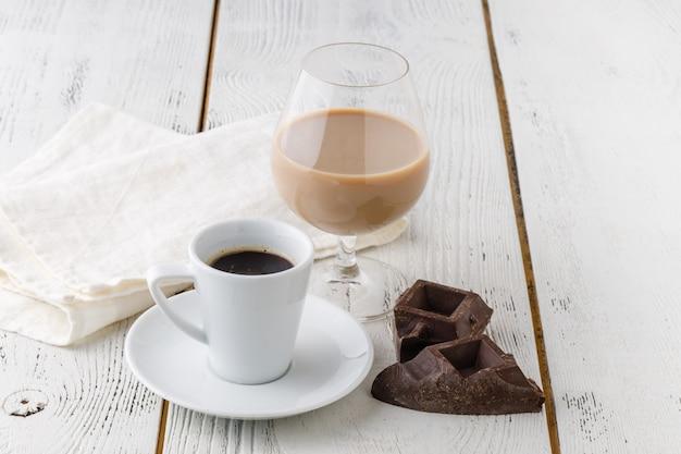 白いセラミックカップとチョコレートビットのコーヒー