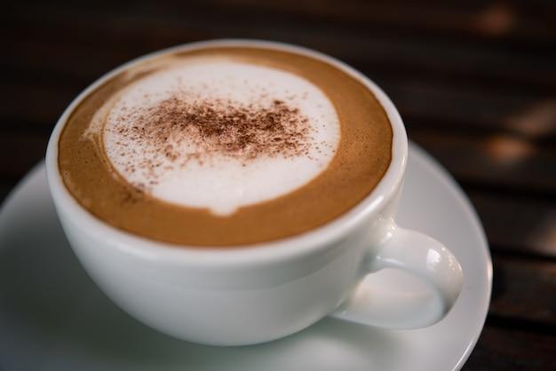 コーヒーショップでのテーブルの上の白いカップでコーヒー