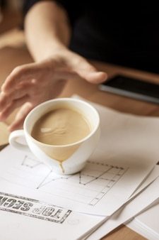 朝のオフィスのテーブルでテーブルの上にこぼれる白いカップのコーヒー