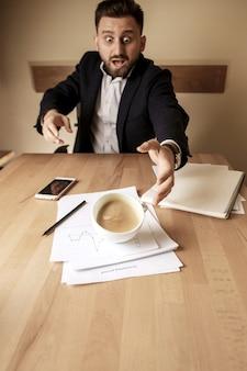 オフィスのテーブルで朝の稼働日のテーブルにこぼれる白いカップのコーヒー