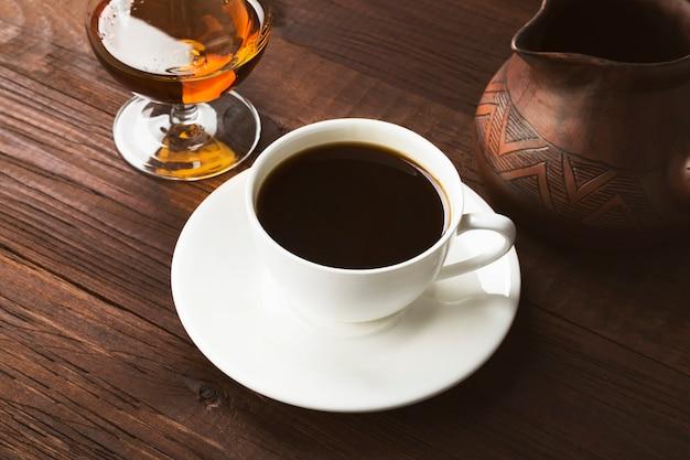 Кофе в белой чашке с коньяком и глиняной туркой