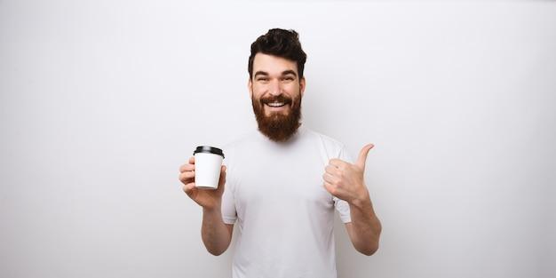 Кофе всегда хорошая идея. бородатый человек показывая как и держа бумажный стаканчик на белой предпосылке.