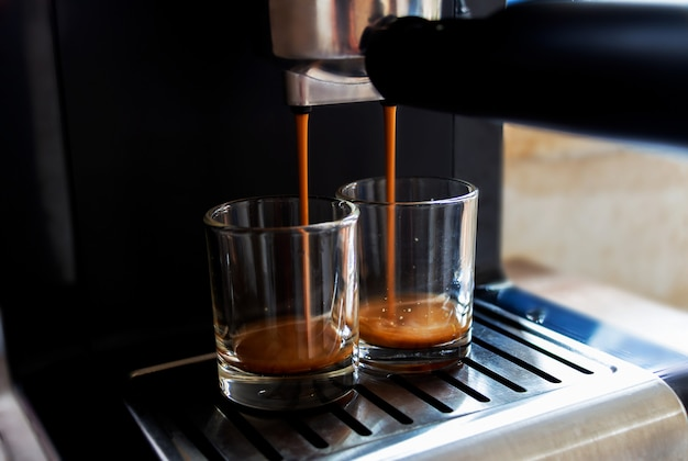 Coffee is flowing from the coffee machine.