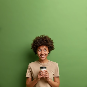 Coffee is never enough. smiling pleased young woman looks above on empty space, holds hot drink in disposable cup, enjoys caffeine beverage, isolated over green wall, notices something up