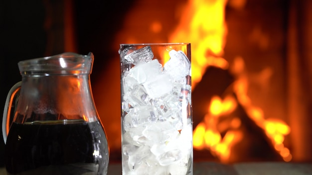 Coffee in jar and glass of ice in front of burning fireplace.