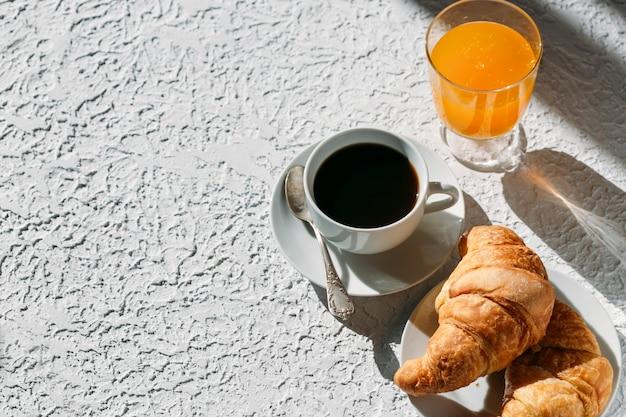 テーブルの上のコーヒージュースとクロワッサン