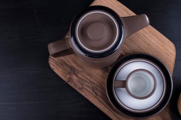 Чайник с чашкой на деревянном блюде.