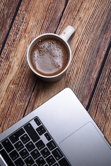 Coffee and laptop on a wooden table