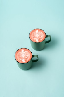 Coffee latte art in a cup of trendy neo mint color.