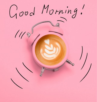 Coffee latte art in pink alarm clock on a pink and dodle good morning