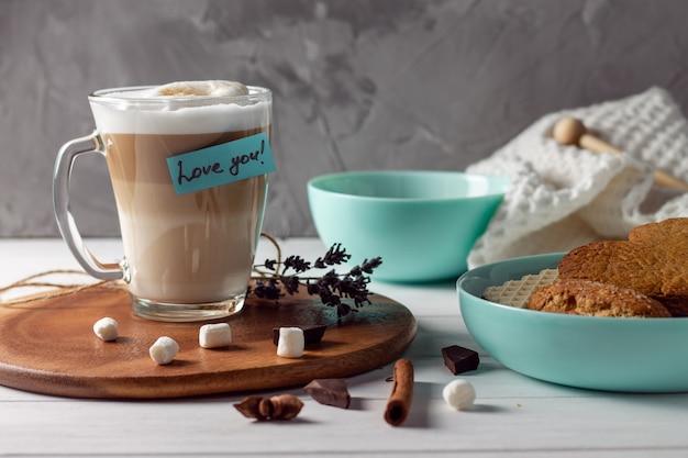 Чашка кофе латте с наклейкой love you на деревянном подносе с бирюзовыми мисками с печеньем и зефиром на серой поверхности стены