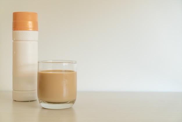 Стакан кофе латте с готовыми к употреблению кофейными бутылками на столе