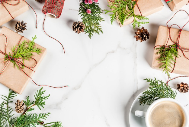 Coffee latte mug with christmas gift or present box wrapped in kraft paper, decorated with christmas tree branches, pine cones, red berries, on white marble table, copy space frame