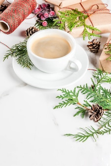 Coffee latte mug with christmas gift or present box wrapped in kraft paper, decorated with christmas tree branches, pine cones, red berries, on white marble table, copy space