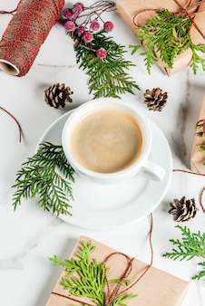 Coffee latte mug with christmas gift wrapped in kraft paper, decorated with christmas tree branches, pine cones and red berries