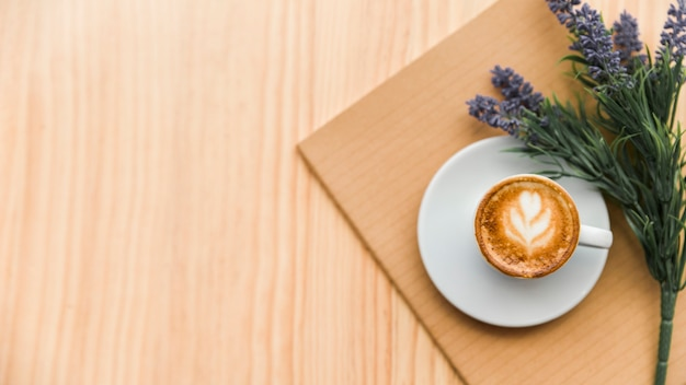 Кофе латте, блокнот и цветок лаванды на деревянном фоне