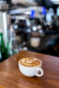Coffee latte on wood table bar with espresso manchine background
