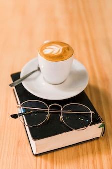 Coffee latte and spectacles over book