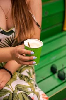 어린 소녀 손에 녹색 종이 컵에 들어갈 커피 라떼