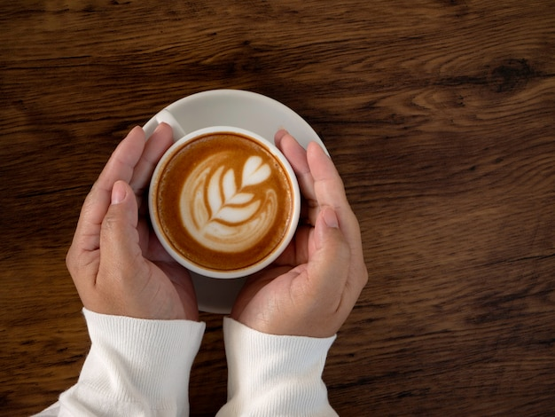 Coffee latte with beautiful latte art on hand