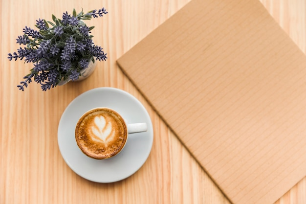 Coffee latte with lavender flower and notebook on wooden background