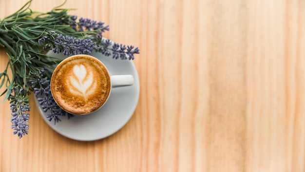 Coffee latte with lavender flower on wooden surface