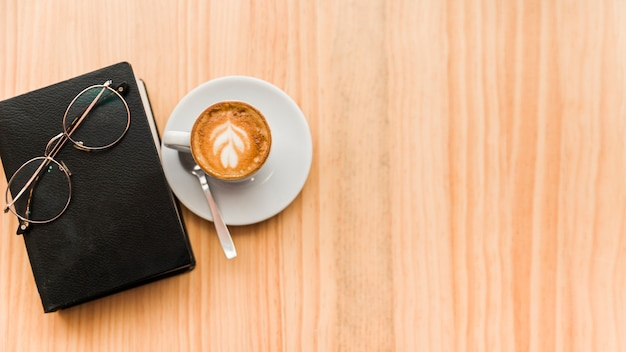 Coffee latte with spectacles and book on wooden background