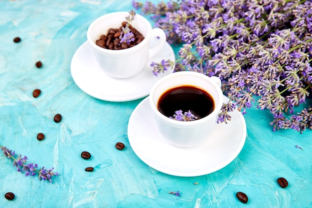 Coffee and lavender flower on blue background from above.