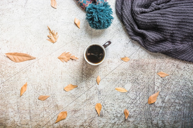 Coffee and leaves near hat and scarf