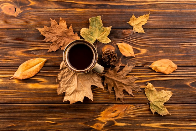 Coffee and leaves on wooden background