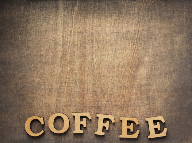 Coffee letters at old wooden background, top view