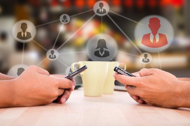 コーヒーのライフスタイル、coffeeshopでの検索やチャットにスマートフォンを使用している人々。