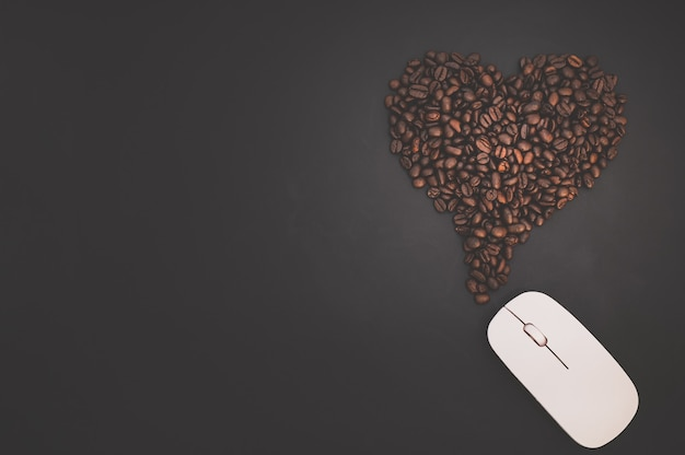Coffee love concept the computer mouse and coffee beans form heart shapes that represent energy of work.